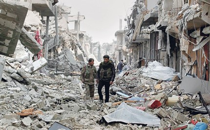 Fighters of the Kurdish People's Protection Units walk past damaged buildings in Kobani
